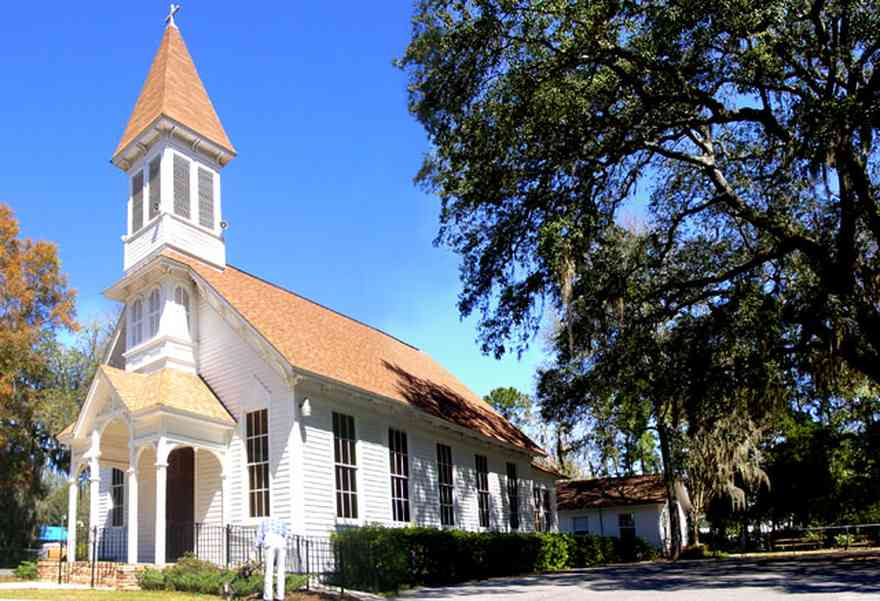 Bagdad:-Methodist-Church_02.jpg:  victorian church, spanish moss, live oak tree, gingerbread trim, gothic revival architectural style, stained glass windows, pointed arch, steep gabled roof, carpenter gothic style