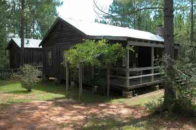Cantonment:-Roy-Hyatt-Environmental-Center-Dog-Trot-House_01.jpg:  dog trot house, wisteria vine, porch, pine tree, board and batten, brick piers