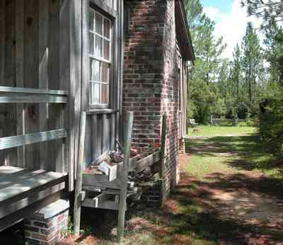 Cantonment:-Roy-Hyatt-Environmental-Center-Dog-Trot-House_07.jpg:  dog trot house, wisteria vine, porch, pine tree, board and batten, wood pile, brick piers