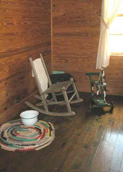 Cantonment:-Roy-Hyatt-Environmental-Center-Dog-Trot-House_11.jpg:  iron bed, quilt, ragdoll, bedroom, wooden walls, wood floor, slop pot, rocking chair