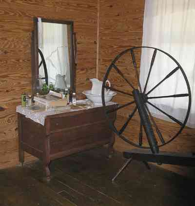 Cantonment:-Roy-Hyatt-Environmental-Center-Dog-Trot-House_12.jpg:  iron bed, quilt, ragdoll, bedroom, wooden walls, wood floor, spinning wheel, dresser, rocking chair