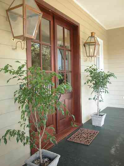 East-Pensacola-Heights:-112-Chipley-Avenue_04.jpg:  mahogany doors, gas lanterns, raised cottage