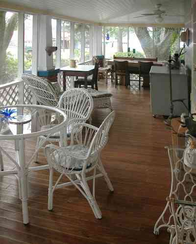 East-Pensacola-Heights:-600-Bayou-Blvd_22.jpg:  wooden floors, wicker porch furniture, screen porch, wide overhang, oak trees