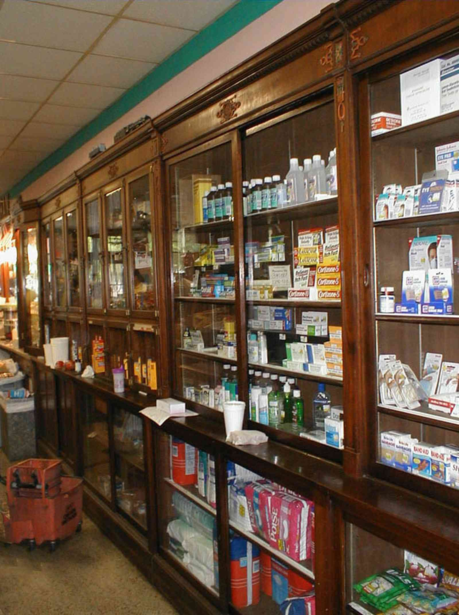 Foley:-Staceys-Drugstore_12.jpg:  drugstore, soda fountain, banana split, glass display cases, soda shop, awning, store front, brick building, art deco architecture, counter, cracker barrel, malts, milkshake, prescription drugs, druggist, card racks