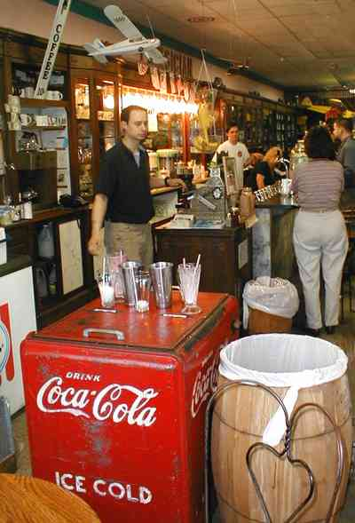 Foley:-Staceys-Drugstore_14.jpg:  drugstore, soda fountain, banana split, glass display cases, soda shop, awning, store front, brick building, art deco architecture, counter, cracker barrel, malts, milkshake, prescription drugs, druggist, card racks,