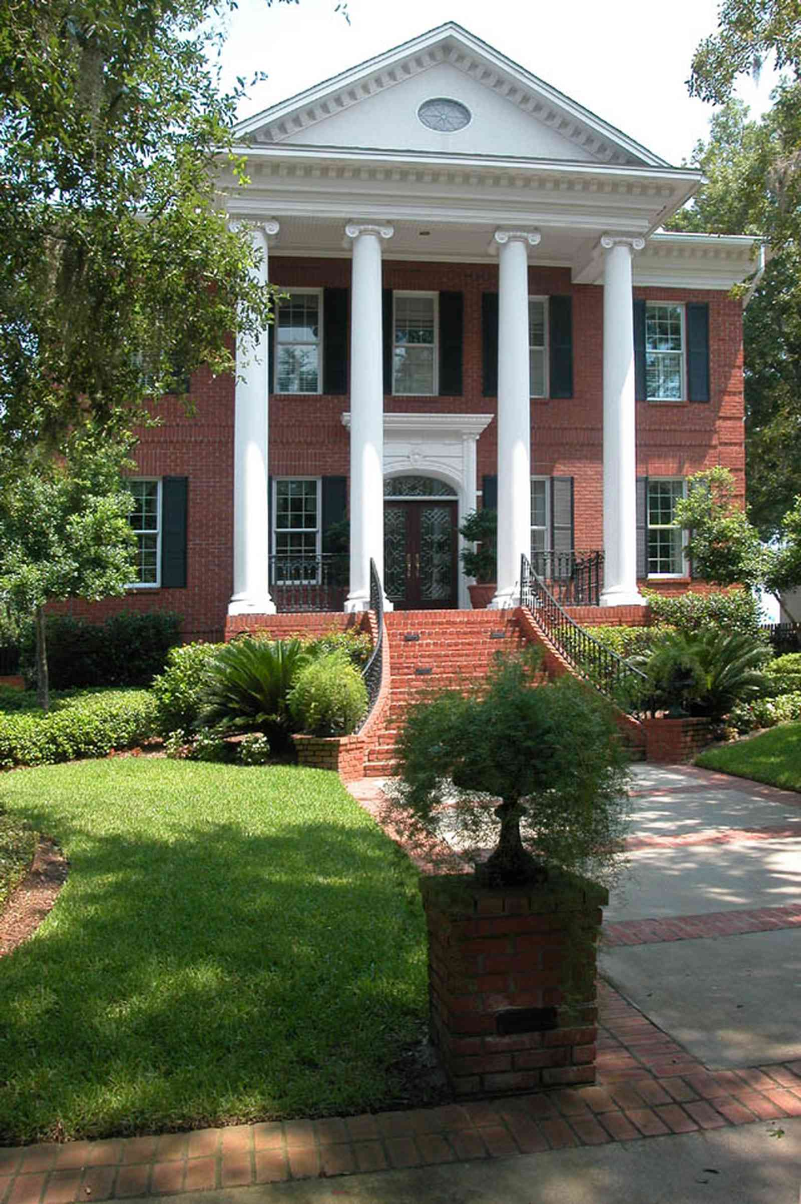 Gulf-Breeze:-506-Kenilworth-Drive_01a-copy.jpg:  red brick mansion, white columns, leaded glass door, mailbox, impatiens, brick wall, spanish moss, oak trees, fern, sidewalk, wrought-iron, doric columns, shutters, porch