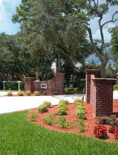 Gulf-Breeze:-706-Fair-Point-Drive_00.jpg:  gate, entrance, formal driveway, lanterns, oak trees, brick columns