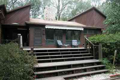 Gulf-Breeze:-9753-Quail-Hollow-Blvd_01.jpg:  deck, steps, awning, 1970's modern home, woods, forest