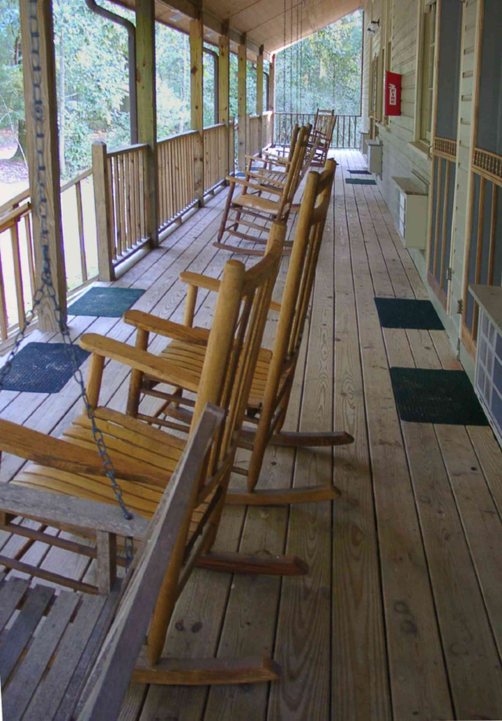 Milton:-Adventures-Unlimited_23.jpg:  porch, rockers, inn, creek, forest, campground