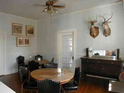 Milton:-Faircloth-Carroll-House-Restaurant_06.jpg:  picket fence, craftsman cottage, restaurant, shutters, ceiling fan, trophy heads, deer head, hunting lodge, french door, milton, front porch