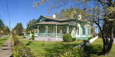 Milton:-Historic-District:-202-Berryhill-Street:-Chadwick-Hartsell-House_04.jpg:  white picket fence, dogwood tree, steamboat house, victorian house