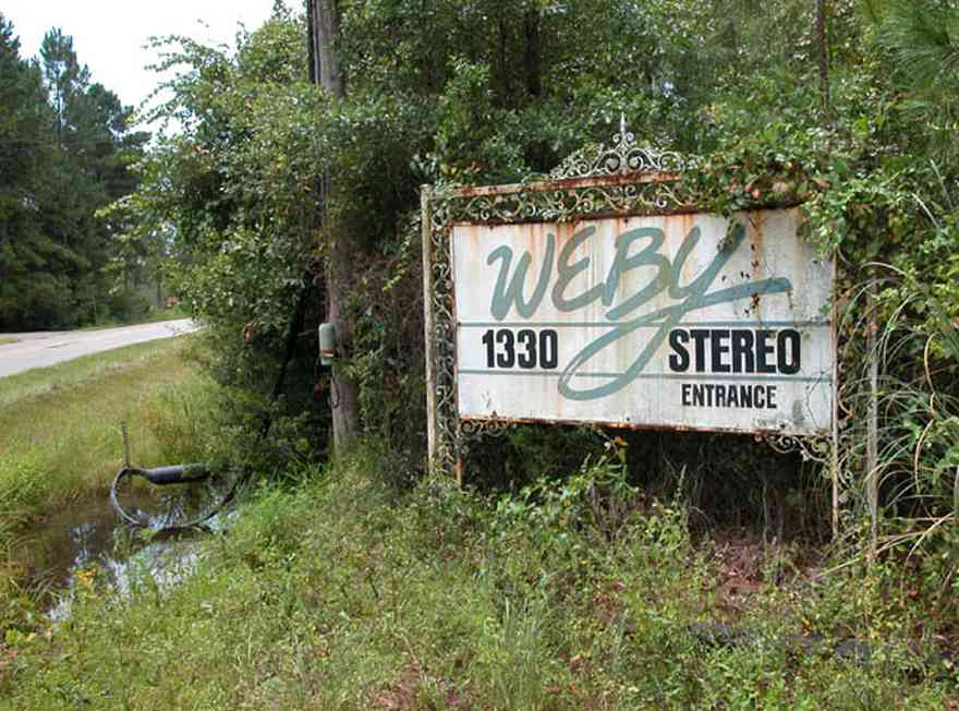 Milton:-WEBY_02.jpg:  sign, wrought iron sign, radio station, pine trees