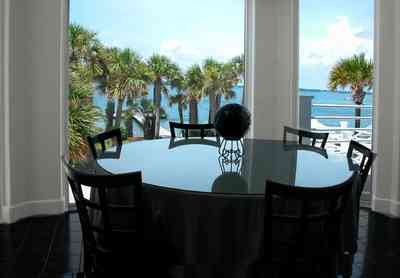 Navarre:-7332-Grand-Navarre-Blvd_13.jpg:  window view, santa rosa sound, palm tree, dining room table, art deco house, glass table
