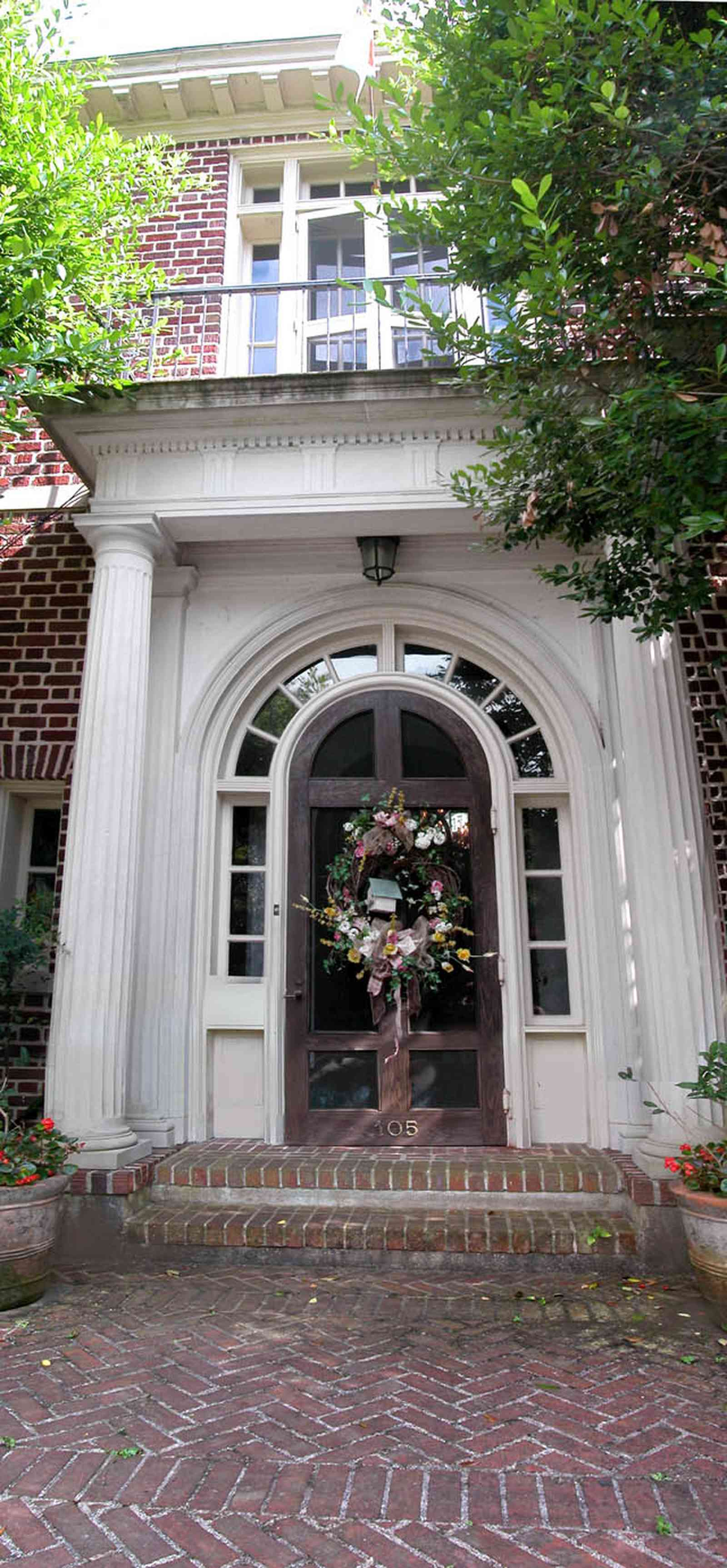 North-Hill:-105-West-Gonzales-Street_020c.jpg:  columns, french colonial architecture, brick sidewalk, geraniums, tile roof