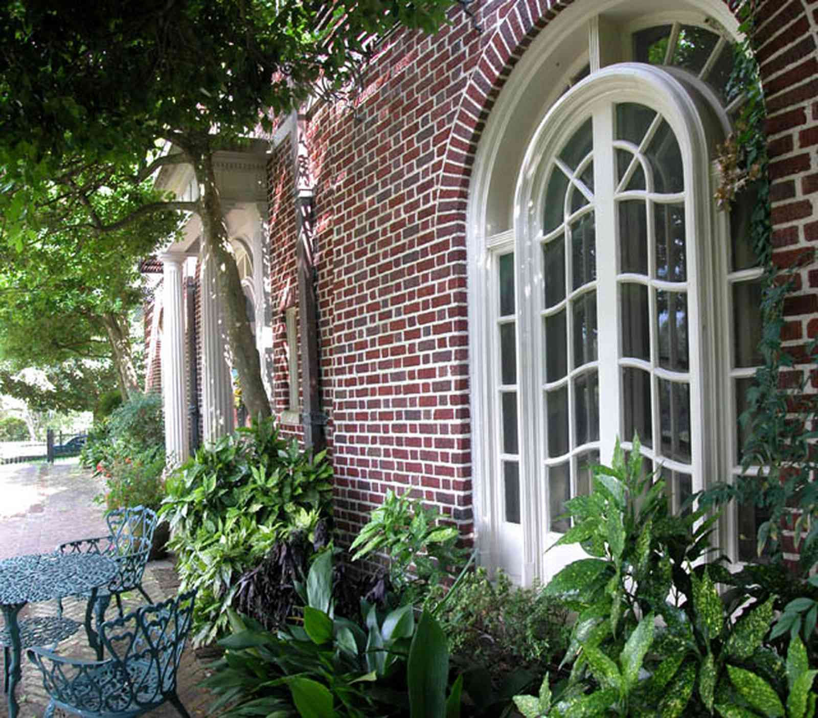 North-Hill:-105-West-Gonzales-Street_02a.jpg:  porch, balcony, oak tree, brick terrace, french colonial architecture, wrought-iron fence