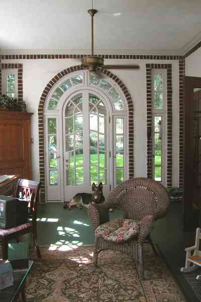 North-Hill:-105-West-Gonzales-Street_09a.jpg:  leaded glass windows, wicker furniture, ceiling fan, brick fireplace, oriental rug, sunroom, german shepard, watch dog