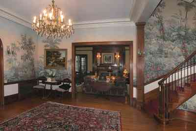 North-Hill:-105-West-Gonzales-Street_25.jpg:  grand foyer, oriental rug, spiral staircase, chandelier, hardwood floors, french colonial architecture