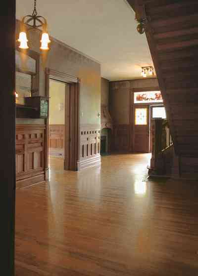 North-Hill:-304-West-Gadsden-Street_14.jpg:  faux walls, stenciled borders, central hall, staircase, oak wainscotting, chandelier, stained glass transom, front door