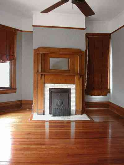 North-Hill:-304-West-Gadsden-Street_27.jpg:  fireplace, wooden mantel, heart pine floors, swag curtains, ceiling fan
