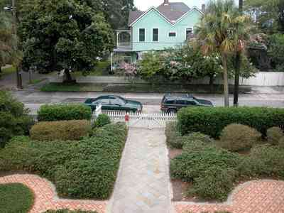North-Hill:-304-West-Gadsden-Street_31.jpg:  formal garden, brick sidewalk, picket fence, victorian house, magnolia tree, crepe myrtle trees, palm tree, north hill preservation district