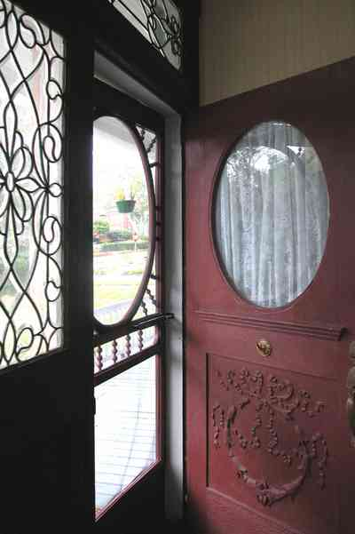 North-Hill:-52-West-Gonzalez-Street_05.jpg:  front door, beveled glass, screen door, oval window, fret work, door carvings, victorian home, transom