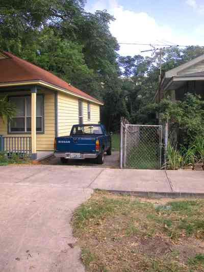 Old-East-Hill:-415-La-Rua-Street_01.jpg:  craftsman cottage, brick street, driveway, oak trees, front porch, chain link fence