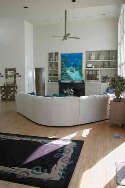 Pensacola-Beach:-Ariola-Drive-Art-Deco-House_29a.jpg:  beach house, marble mantle, fireplace, waterfront property, ceiling fan, sectional leather sofa, area rug, shelves, wood floors, beach front property