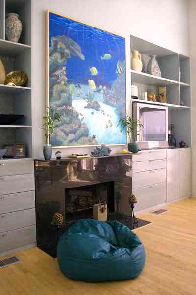Pensacola-Beach:-Ariola-Drive-Art-Deco-House_29b.jpg:  bean bag chair, marble mantle, tv set, sealife painting, wood floor, built-in shelves, beachfront home, knick-knacks