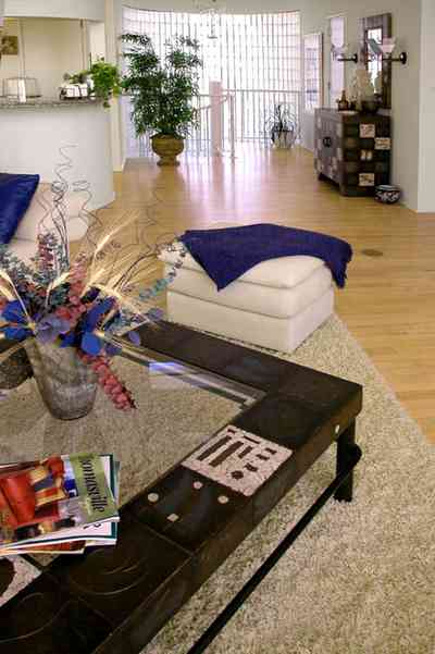 Pensacola-Beach:-Ariola-Drive-Art-Deco-House_30b.jpg:  beach front home, gulf of mexico, coffee table, foot stool, hassock, leather sofa, area rug, wood floors, spiral staircase, flower arrangement