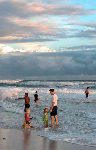 Pensacola-Beach:-Sunset_01.jpg:  mixed skies, surf, surfers, bathers, children, gulf of mexico, sunset