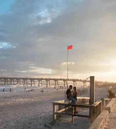 Pensacola-Beach:-Sunset_02a.jpg:  warning flag, surf, surfer, beach, sand, sunset, fishing pier, gulf of mexico