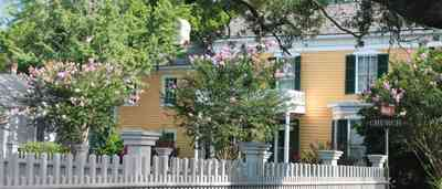 Pensacola:-Historic-Pensacola-Village:-Dorr-House_10.jpg:  picket fence, folk victorian house, wood shingle roof, wood shake roof, oak tree, crepe myrtle trees, old christ church