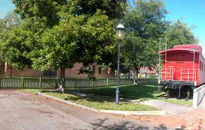 Pensacola:-Historic-Pensacola-Village:-Museum-Of-Industry_03.jpg:  locomotive, caboose, oak tree, picket fence, brick sidewalk