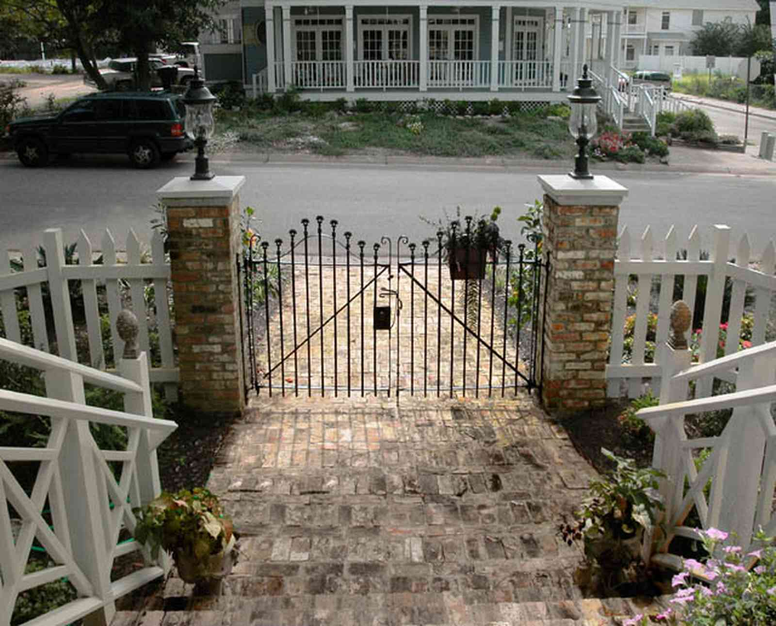 Pensacola:-Seville-Historic-District:-202-Cevallos-Street_02.jpg:  wrought-iron gate, brick pillars, picket fence, brick sidewalk
