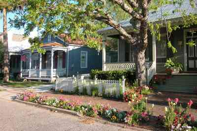 Pensacola:-Seville-Historic-District:-226-East-Intendencia-Street_02.jpg:  snapdragons, cabbages, ferns, pecan tree, strawberry plants, peturnias, white picket fence, victorian front porch, pyramid roof, four-square georgian architectural style, victorian cottage, historic preservation, historic district, brick sidewalk,