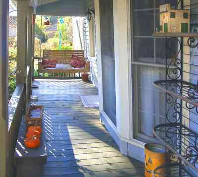 Pensacola:-Seville-Historic-District:-227-East-Intendencia-Street_03.jpg:  halloween pumpkin, wrought-iron shelves, porch swing, porch, bay window
