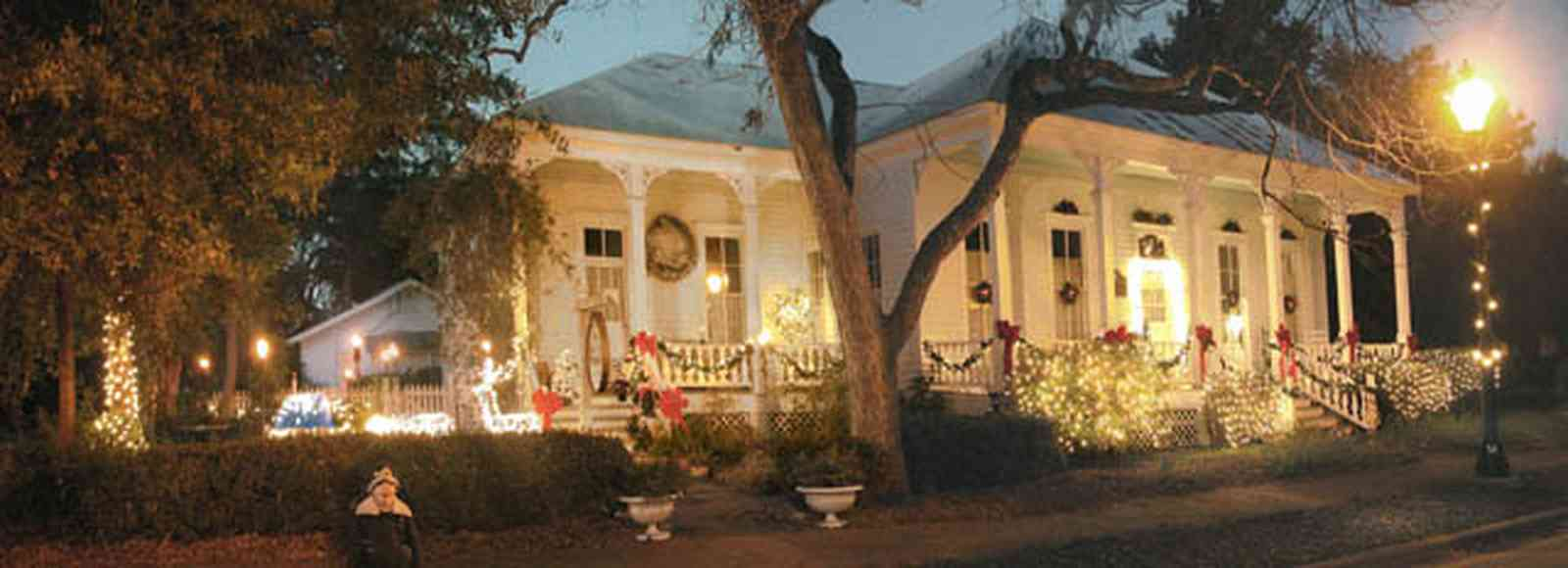 Pensacola:-Seville-Historic-District:-434-East-Zaragoza-Street_04.jpg:  christmas decoration, garland, festive, oak tree, front porch, four-square georgian architecture, wreath, fountain, pyramid roof, tin roof, gingerbread trim, street light,, underground power, brick sidewalk