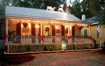 Pensacola:-Seville-Historic-District:-Lisa-Minshew-Attorney_04.jpg:  garland, bows, candy canes, american flag, holiday lights, wreath, shutters, tin roof, deer, fireplace, front porch, victorian cottage