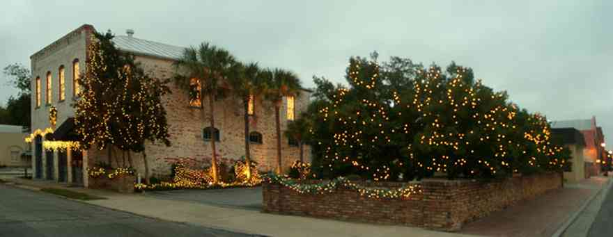 Pensacola:-Seville-Historic-District:-Michael-Mabire-Company_02.jpg:  christmas decorations, garland, bows, wreath, palm trees, awning, brick sidewalks, brick wall