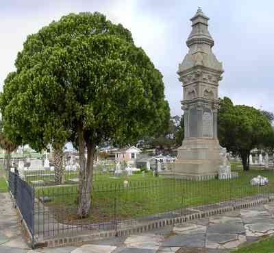 Pensacola:-Seville-Historic-District:-St-Michael-Cemetery_05.jpg:  wrought-iron fence, tiled sidewalks, cemetery, cedar trees