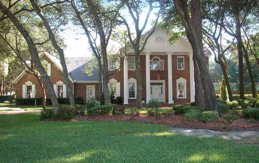 Scenic-Highway:-4450-Devereau-Drive_02.jpg:  colonial architectural style, white columns, shutters, crown molding pediment, circular driveway, carriage lamp, oak trees