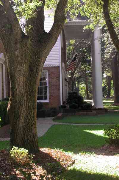 Scenic-Highway:-4450-Devereau-Drive_04.jpg:  colonial architectural style, white columns, shutters, crown molding pediment, circular driveway, carriage lamp, oak trees