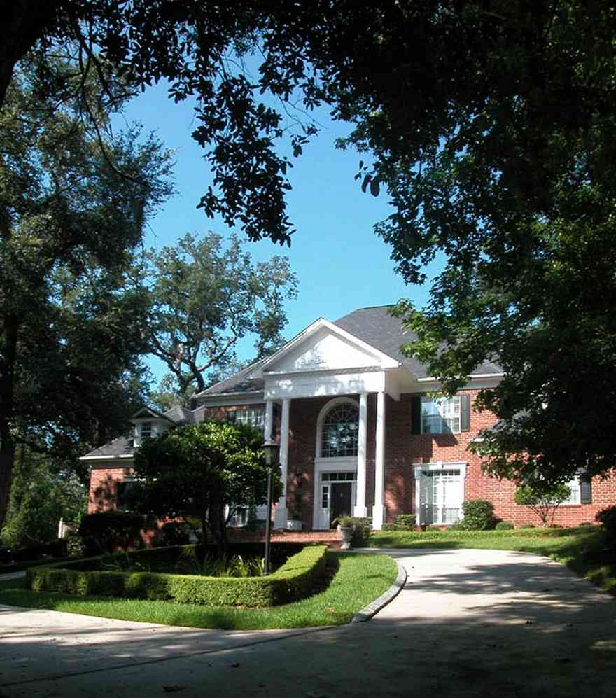 Scenic-Highway:-4641-Canopy-Road_01.jpg:  colonial architectural style, white columns, shutters, crown molding pediment, circular driveway, carriage lamp, sycamore tree, box hedge, oak trees