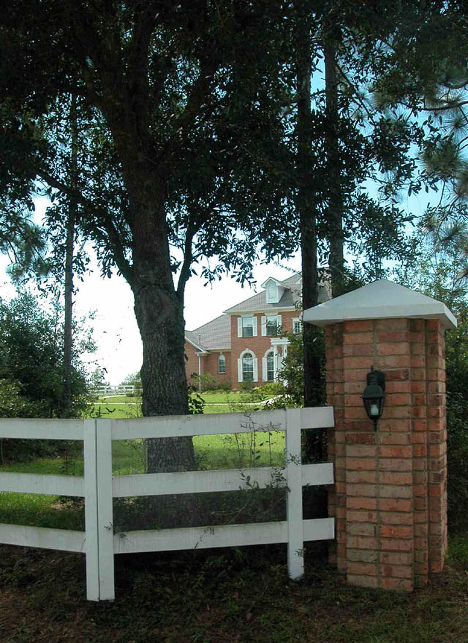 Cantonment:-Milestone:-Red-Brick-Mansion-A_00.jpg:  white fence, board fence, brick pillar, gate entrance, red brick house, circular driveway