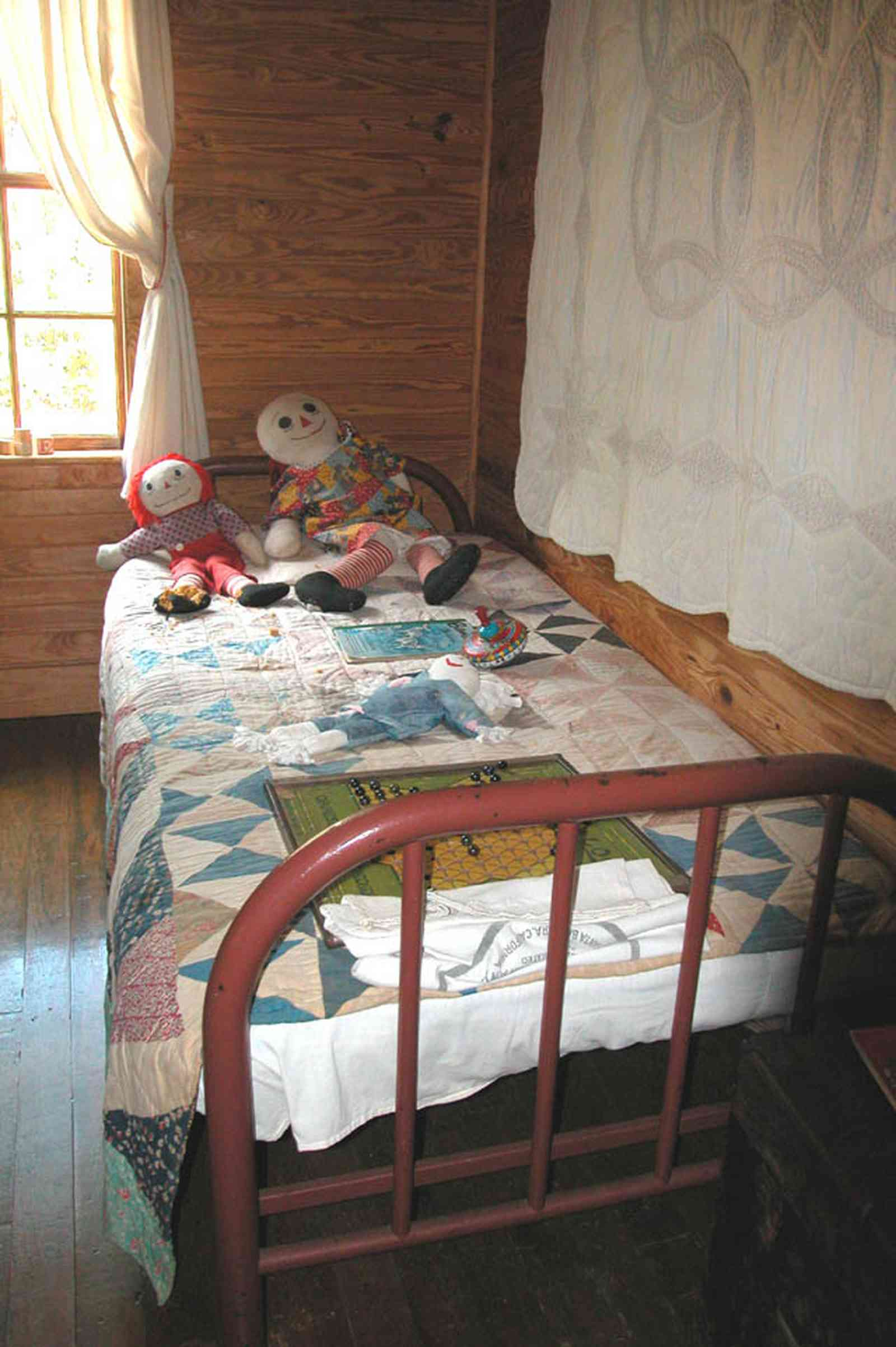 Cantonment:-Roy-Hyatt-Environmental-Center-Dog-Trot-House_10.jpg:  iron bed, quilt, ragdoll, bedroom, wooden walls, wood floor, rocking chair