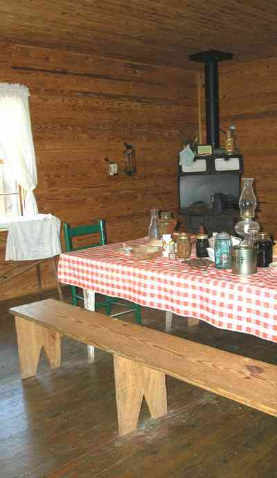 Cantonment:-Roy-Hyatt-Environmental-Center-Dog-Trot-House_17.jpg:  iron bed, quilt, ragdoll, bedroom, wooden walls, wood floor, bench, lantern, wood burning stove, ladder-back chair, ironing board, red checked tablecloth, oil lantern, rocking chair
