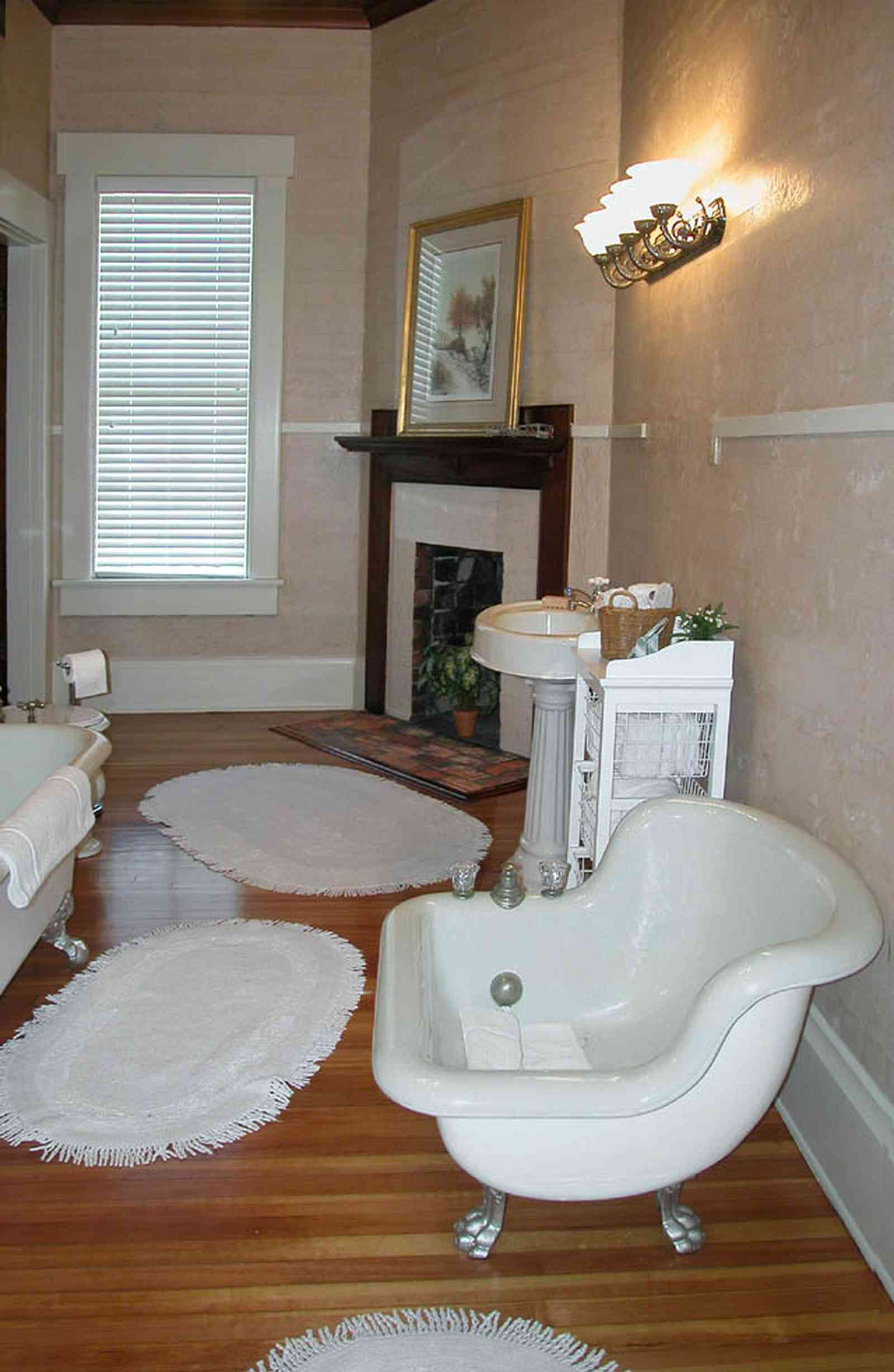 Century:-Tannenheim_01n.jpg:  bathtub, fireplace, pedestal sink, wainscotting, wooden floors, ventian blinds, fringed rugs