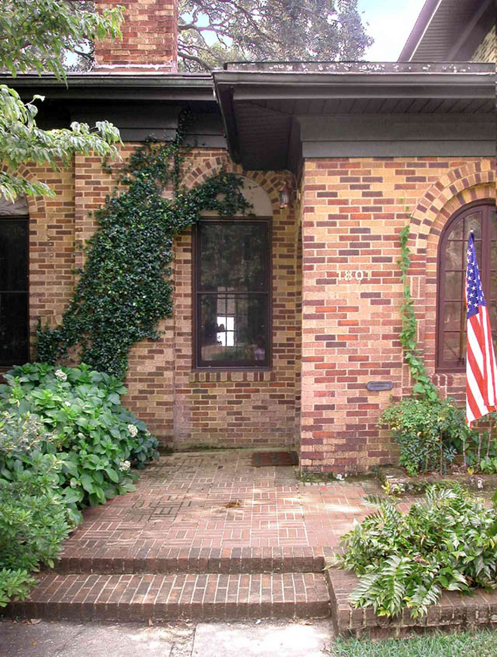 East-Hill:-1801-East-La-Rua-Street_02.jpg:  brick house, front steps, american flag, ivy covered wwall, hydranga bush, brick step