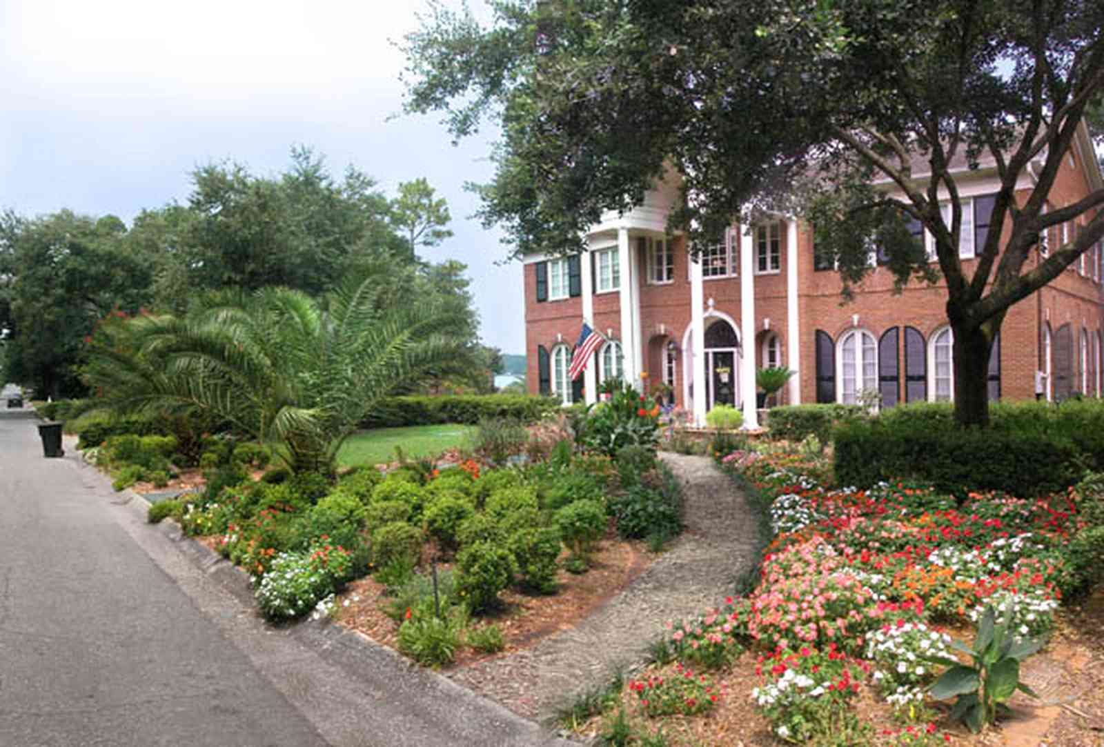 East-Hill:-2000-Whaley-Avenue_02.jpg:  red brick house, impatiens, box hedges, oak trees, columns, shutters, brick veneer, flower garden,