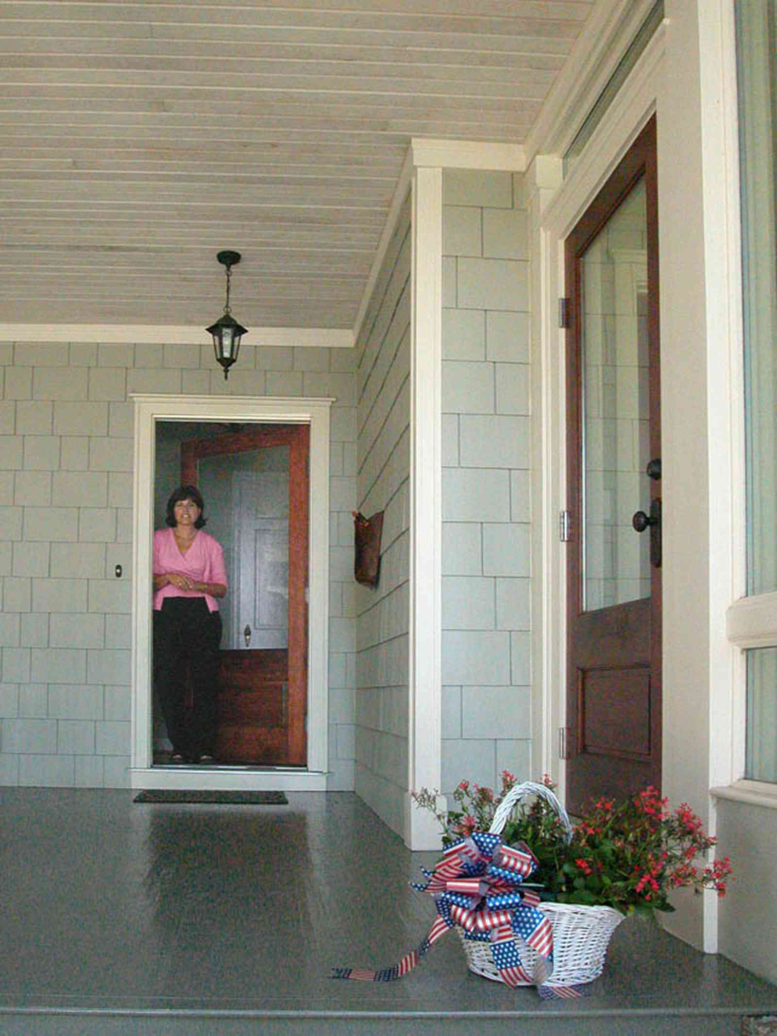 East-Hill:-2109-Whaley-Drive_03a.jpg:  front door, shingle siding, wooden porch floor, basket of flowers, beaded wooden ceiling